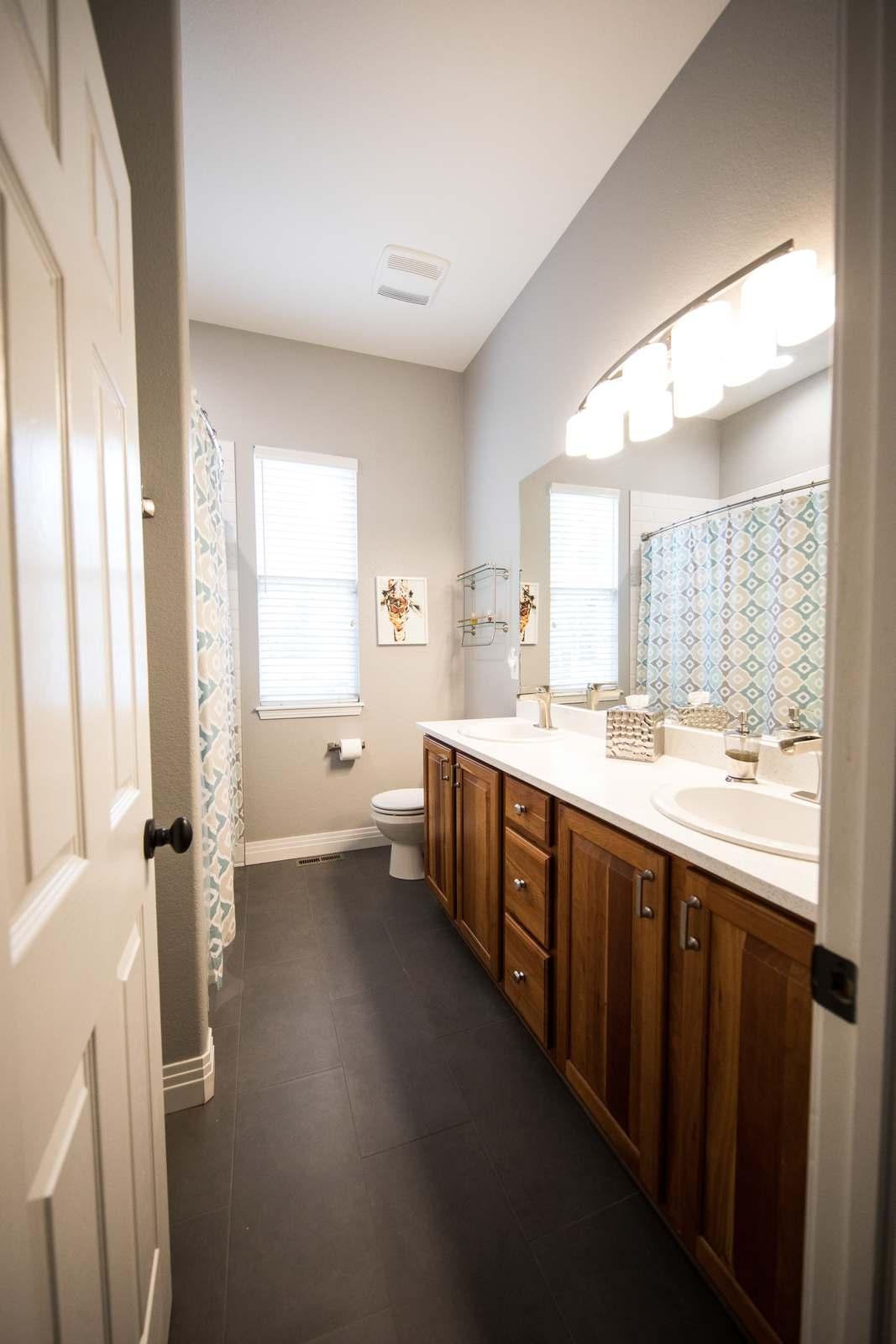 Jasna łazienka z drewnianymi meblami i oświetleniem nad lustrem